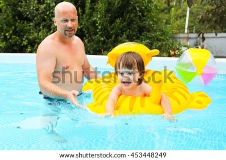Happy little boy on inflatable toy swimms with his father in swimming pool