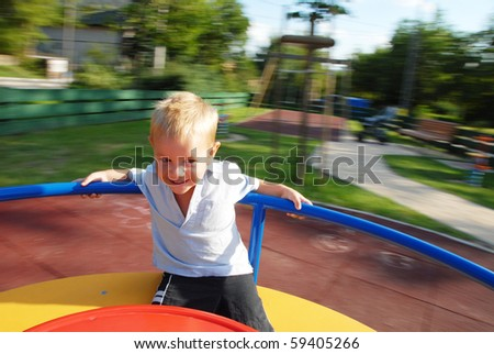 happy little boy on the carousel - stock photo