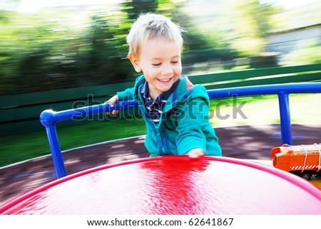 happy little boy on the carousel - stock photo