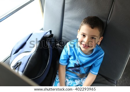 Happy little boy on the school bus going to summer camp or school - stock photo