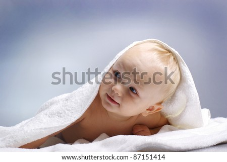 Happy little boy on white blanket - stock photo