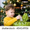 Happy little boy opening Chrismas present at Christmas Eve under the Christmas tree. - stock photo