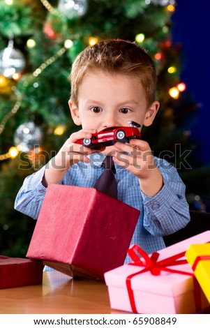 Happy little boy opening Christmas gifts near New Year's tree - stock photo