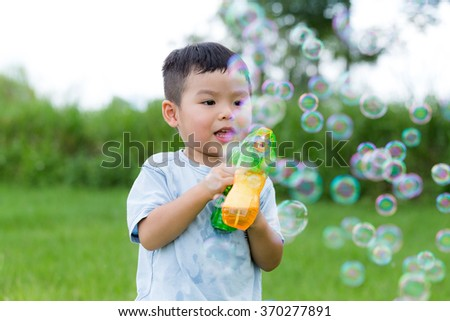 Happy little boy play with bubble blower at outdoor - stock photo