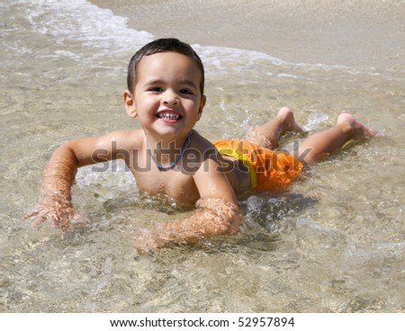 Happy little boy playing at the beach - stock photo