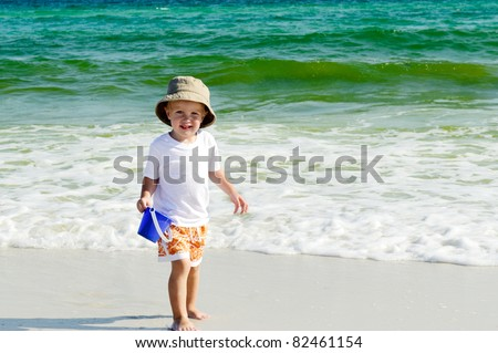 Happy little boy playing by the sea