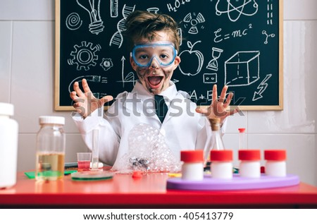 Happy little boy playing excited with experiment results - stock photo