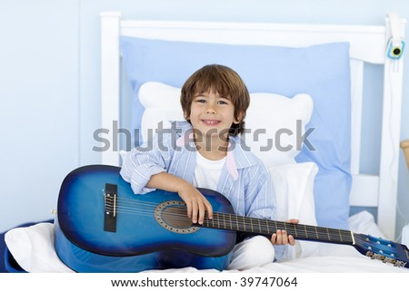 Happy little boy playing guitar sitting in bed - stock photo