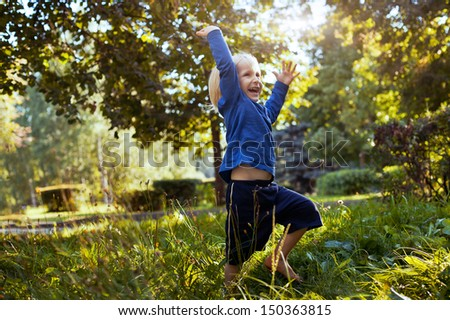 happy little boy playing in the park outdoors - stock photo
