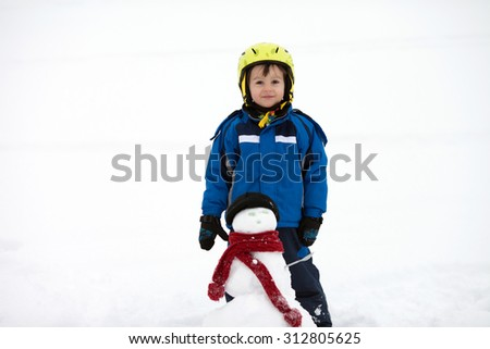 Happy little boy playing in the snow while snowing, helmet, scarf and gloves