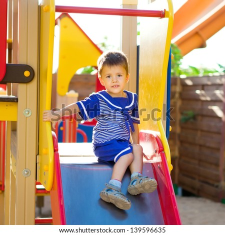 Happy little boy playing on playground. Summer park. Outdoors.  - stock photo