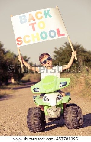 Happy little boy playing on road at the day time. He driving on quad bike in the park. Child having fun on the nature. Concept of the boy are ready to go to school. - stock photo