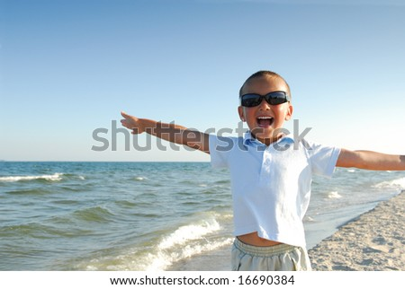 Happy little boy playing  on the beach - stock photo