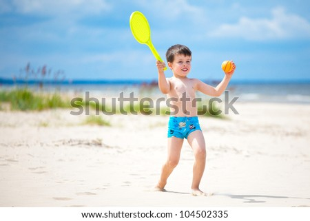 Happy little boy playing on tropical beach - stock photo