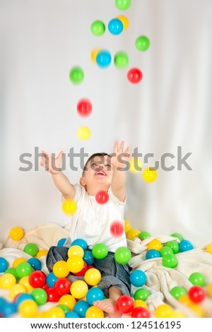 Happy little boy playing with a ball falling - stock photo