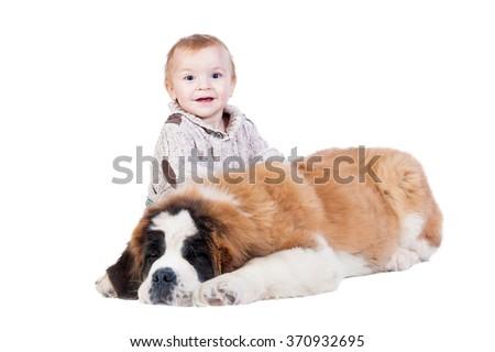 Happy little boy playing with a saint bernard puppy  - stock photo