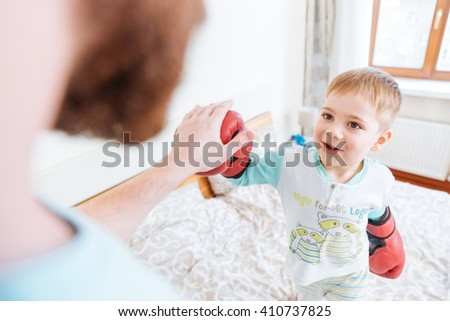 Happy little boy playing with his father using boxing gloves