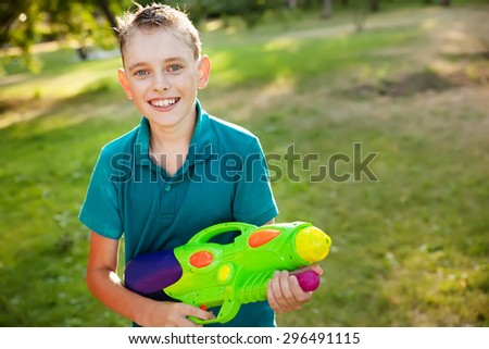 happy little boy playing with water gun - stock photo