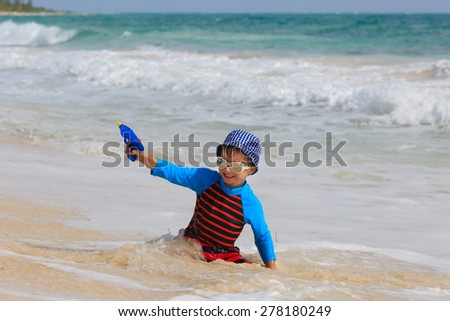 happy little boy playing with water gun on summer beach - stock photo
