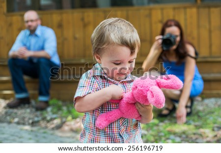 Happy little boy plays with a pink plush Easter bunny rabbit. Father watches in the background and his mother, holding a camera, takes a picture of the moment outside in a garden.  Park of a series.  - stock photo
