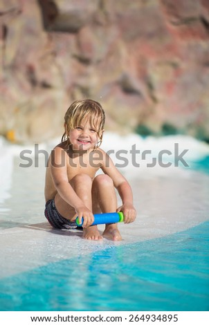 Happy little boy plays with water toy in the swimming pool  - stock photo