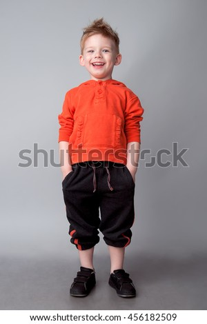 Happy little boy poses on a gray background. He is dressed sport suit. Sport Style. Studio shot - stock photo