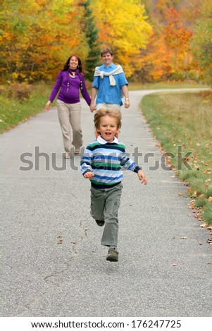 Happy little boy running in the park. His parents watching him from a distance.