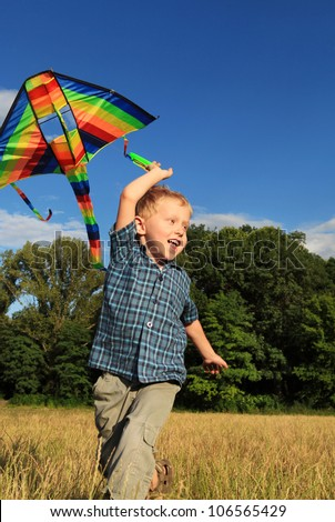 Happy little boy running with bright kite over his head - stock photo