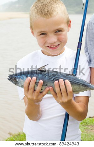 happy little boy showing a fish he just caught