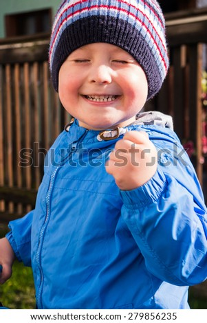 happy little boy showing fist in a gesture of victory - stock photo