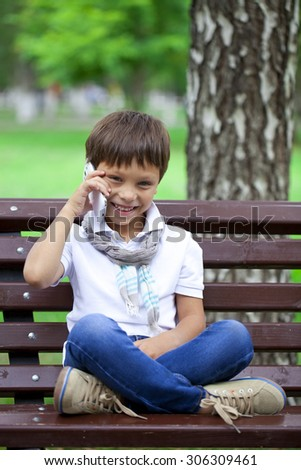 Happy little boy sits on a bench and calling by mobile phone on a background of summer park