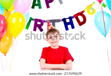 Happy little boy sitting at the table having fun in a birthday party - isolated on a white.