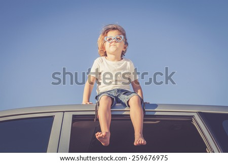 Happy little boy sitting in the car at the day time - stock photo