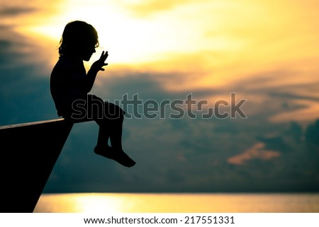 happy little boy sitting on beach at the dawn time - stock photo