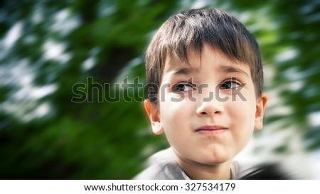 Happy little boy smiling on blurred background - stock photo