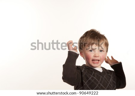 happy little boy smiling throwing arms up in air
