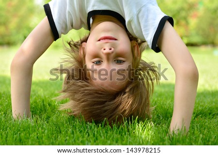 Happy little boy standing upside down on green grass in spring park - stock photo