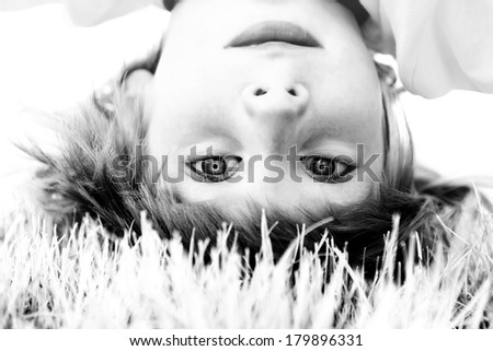 Happy little boy standing upside down on green grass in spring park, black and white - stock photo