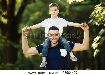 happy little boy stretching out hands while his father carrying him on shoulders - stock photo