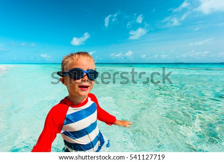 happy little boy swimming on tropical beach