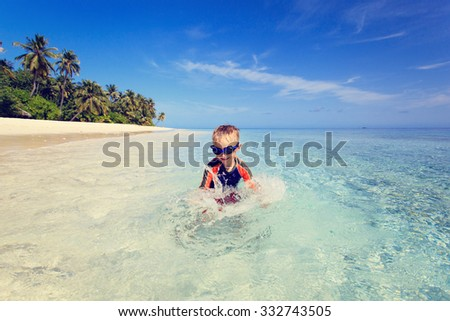 happy little boy swimming on tropical beach vacation - stock photo