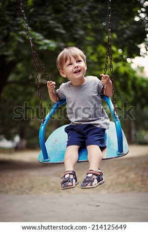 Happy little boy swinging on a swing outdoors in the garden or park smiling with enjoyment as he looks up watching something off frame - stock photo