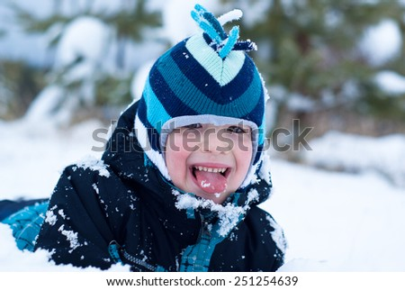 Happy little boy tries to eat snow - stock photo