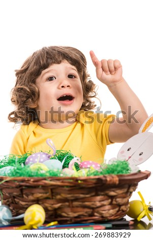 Happy little boy two years age pointing up  to white space and sitting at table with Easter eggs - stock photo