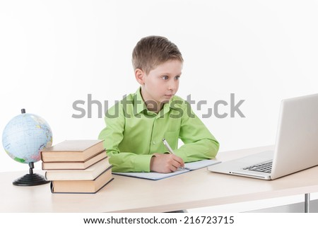 Happy little boy using laptop at table. cute schoolboy sitting at desk and writing in notebook