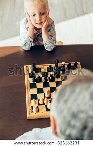 Happy little boy waiting for his grandfather to make their move - stock photo
