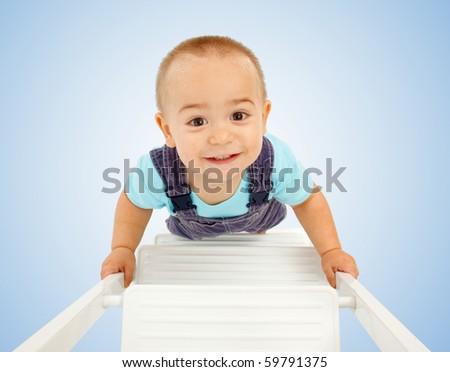 Happy little boy walking up on white ladder - stock photo