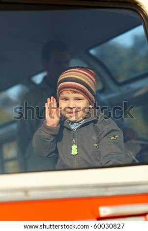 Happy little boy waving hand, through the window view. - stock photo