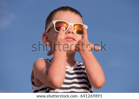 happy little boy wearing sunglasses with sea sunset reflection and striped shirt touching his sunglasses with fingers on blue sky background
