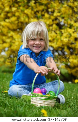 Happy  little boy with basket full of colorful easter eggs outdoors - stock photo